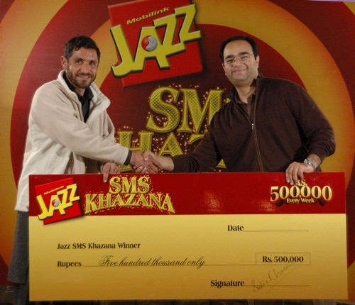 Lahore: Wasif Mustafa, Director Value Added Services Mobilink (R) handing over a cheque to Tariq Mehmood (L), the lucky winner of Mobilink Jazz SMS Khazana scheme